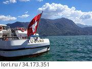 Купить «Lake Lugano on a spring sunny day. View of a passenger ship decorated with the Swiss flag. Lugano, canton of Ticino, Switzerland, Europe.», фото № 34173351, снято 17 апреля 2018 г. (c) Bala-Kate / Фотобанк Лори