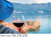 Caucasian woman wearing blue hat standing in an apartment balcony and holding glass with red wine looking at the Budva town below, Montenegro. Стоковое фото, фотограф Zoonar.com/Pawel Opaska / easy Fotostock / Фотобанк Лори