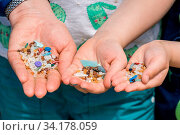 Family of mother and children holding and showing small tiny harmful plastic microbeads collected on the beach in Zante, Zakynthos, Greece. Стоковое фото, фотограф Zoonar.com/Pawel Opaska / easy Fotostock / Фотобанк Лори