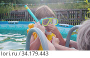 A little boy in underwater mask about to swim in the inflatable pool -his grandmother help putting a tube in his mouth. Стоковое видео, видеограф Константин Шишкин / Фотобанк Лори