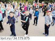 Купить «Первоклашки на дне здоровья танцуют и выполняют спортивные упражнения у стен школы», эксклюзивное фото № 34179875, снято 14 июля 2020 г. (c) Кузин Алексей / Фотобанк Лори