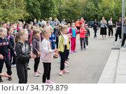 Купить «Первоклашки на дне здоровья танцуют и выполняют спортивные упражнения у стен школы», эксклюзивное фото № 34179879, снято 14 июля 2020 г. (c) Кузин Алексей / Фотобанк Лори