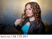 Portrait of plump curvy girl with long curly hair by the water of a lake at sunset with the sun on the horizon. Стоковое фото, фотограф Кривошеина Елена Леонидовна / Фотобанк Лори