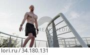 Купить «Sporty Caucasian man training on a bridge», видеоролик № 34180131, снято 30 мая 2019 г. (c) Wavebreak Media / Фотобанк Лори
