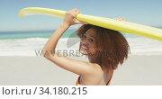 African American woman holding surfboard on her head. Стоковое видео, агентство Wavebreak Media / Фотобанк Лори