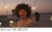 Mixed race woman playing with fire on the beach. Стоковое видео, агентство Wavebreak Media / Фотобанк Лори