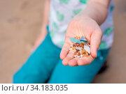 Little girl holding small tiny harmful plastic microbeads collected on the beach in Zante, Zakynthos, Greece. Стоковое фото, фотограф Zoonar.com/Pawel Opaska / easy Fotostock / Фотобанк Лори