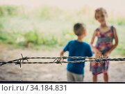 Купить «Brother and sister playing behind the barbed wired fence gates to the Banstead woods in Surrey, England», фото № 34184831, снято 4 августа 2020 г. (c) easy Fotostock / Фотобанк Лори