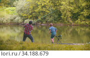 Two brothers on fishing - man pulling the rod and his little brother stands from the chair and comes near him. Стоковое видео, видеограф Константин Шишкин / Фотобанк Лори