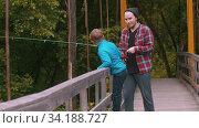 Two brothers standing on the rope bridge and fishing. Стоковое видео, видеограф Константин Шишкин / Фотобанк Лори