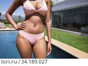 Mid section of woman standing by the pool. Стоковое фото, агентство Wavebreak Media / Фотобанк Лори