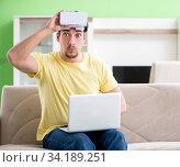 Купить «Young man with virtual reality goggles», фото № 34189251, снято 8 мая 2018 г. (c) Elnur / Фотобанк Лори