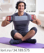 Купить «Man doing sports with resistance band and listening to music», фото № 34189575, снято 5 декабря 2017 г. (c) Elnur / Фотобанк Лори