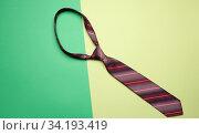 Купить «Knotted silk manâ.s tie on a green background, top view.», фото № 34193419, снято 6 июля 2020 г. (c) easy Fotostock / Фотобанк Лори