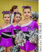 Moscow, Russia - December 22, 2019: Little girls sport dancers in purple leotards with pom poms, direct look at camera. Редакционное фото, фотограф Андрей Копылов / Фотобанк Лори