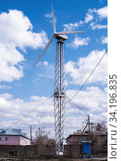 Wind turbine in the village against a blue sky with clouds. Photo taken in Russia, in the city of Orenburg. Стоковое фото, фотограф Вадим Орлов / Фотобанк Лори