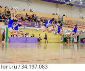 Moscow, Russia - December 22, 2019: Girls with pom poms in blue sports uniforms jump high, performing cheerleader trick. Редакционное фото, фотограф Андрей Копылов / Фотобанк Лори
