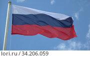 Российский флаг на ветру на фоне голубого неба. Стоковое видео, видеограф Виктор Карасев / Фотобанк Лори