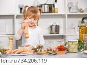 Купить «Girl is salting vegetables dish in the kitchen», фото № 34206119, снято 27 января 2018 г. (c) Яков Филимонов / Фотобанк Лори