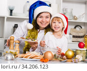 Купить «Girl and her mother are demonstraiting dish for holiday in the kitchen», фото № 34206123, снято 27 января 2018 г. (c) Яков Филимонов / Фотобанк Лори
