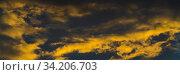 Купить «Golden fluffy clouds illuminated by disappearing rays at sunset and dark thunderclouds floating across sunny blue sky to change season weather», фото № 34206703, снято 8 ноября 2019 г. (c) А. А. Пирагис / Фотобанк Лори