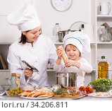 Купить «Girl and her mother are cooking soup together and adding spices», фото № 34206811, снято 27 января 2018 г. (c) Яков Филимонов / Фотобанк Лори
