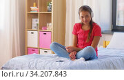Купить «happy girl in headphones with smartphone at home», видеоролик № 34207843, снято 14 июня 2020 г. (c) Syda Productions / Фотобанк Лори