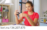 Купить «girl with smartphone distracting from homework», видеоролик № 34207875, снято 14 июня 2020 г. (c) Syda Productions / Фотобанк Лори