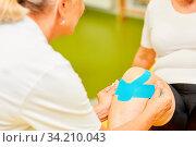 Physiotherapeutin befestigt ein Kinesio Tape am Knie eines Patienten zur Schmerzlinderung. Стоковое фото, фотограф Zoonar.com/Robert Kneschke / age Fotostock / Фотобанк Лори