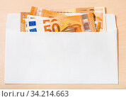Several fifty euro notes in open mail envelope on wooden table. Стоковое фото, фотограф Zoonar.com/Valery Voennyy / easy Fotostock / Фотобанк Лори