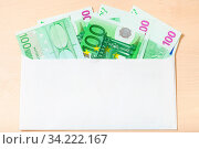 Fan from several one hundred euro notes in open mail envelope on wooden table. Стоковое фото, фотограф Zoonar.com/Valery Voennyy / easy Fotostock / Фотобанк Лори