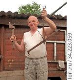 Мужчина держит в руках топор и старые хозяйственные механические весы. Сельский быт. Стоковое фото, фотограф Ирина Борсученко / Фотобанк Лори
