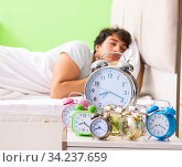 Young man having trouble waking up in early morning. Стоковое фото, фотограф Elnur / Фотобанк Лори