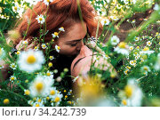 Guy and the girl lie in a field of daisies. Стоковое фото, фотограф Zoonar.com/Oleksii Hrecheniuk / easy Fotostock / Фотобанк Лори