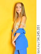 Torso Portrait of the beautiful blonde woman in blue costume. Studio shooting with yellow background. Стоковое фото, фотограф Zoonar.com/© Dmitry Raikin / easy Fotostock / Фотобанк Лори