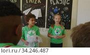 Two girls wearing recycle symbol tshirt holding plastic bottle and bag. Стоковое видео, агентство Wavebreak Media / Фотобанк Лори