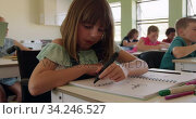Physically challenged girl writing in her notebook in the class. Стоковое видео, агентство Wavebreak Media / Фотобанк Лори