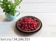 Спелая малина в тарелке и пучок мелиссы в чашке на белом столе. Стоковое фото, фотограф Наталья Гармашева / Фотобанк Лори