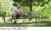 Купить «Senior man tying his shoe laces while sitting on a bench in the park», видеоролик № 34246751, снято 16 октября 2019 г. (c) Wavebreak Media / Фотобанк Лори