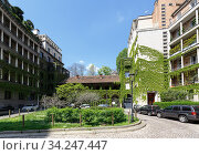 View of the Sant Erasmo Square on a spring sunny day. High-rise buildings overgrown with plants. City of Milan, region of Lombardy, Italy, Europe. (2018 год). Редакционное фото, фотограф Bala-Kate / Фотобанк Лори