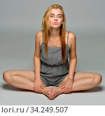 Portrait of the sexy beautiful woman in short overall is sitting on the floor in studio with grey background. Стоковое фото, фотограф Zoonar.com/© Dmitry Raikin / easy Fotostock / Фотобанк Лори