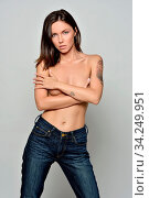 Beautiful woman only in jeans posing in studio with grey background. She is crossing arms on her bosom. Стоковое фото, фотограф Zoonar.com/© Dmitry Raikin / easy Fotostock / Фотобанк Лори