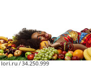 African American Black woman smiles at the camera while lying among fruits in studio. Стоковое фото, фотограф Алексей Кузнецов / Фотобанк Лори