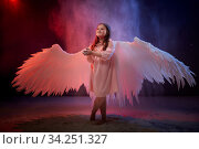 Small young model girl with white wings posing and dancing in dark black studo during photoshoot with flour or dust and colour light. Actress in performance about struggle between good and evil. Стоковое фото, фотограф Кривошеина Елена Леонидовна / Фотобанк Лори