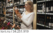 Portrait of mature woman visiting winehouse in search of bottle of good wine. Стоковое видео, видеограф Яков Филимонов / Фотобанк Лори