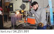 Portrait of confident man mechanic using drilling machine in workshop. Стоковое видео, видеограф Яков Филимонов / Фотобанк Лори