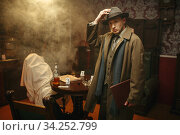 Puzzled detective in coat and hat, crime scene. Стоковое фото, фотограф Tryapitsyn Sergiy / Фотобанк Лори