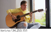 Купить «young man playing guitar sitting on windowsill», видеоролик № 34253151, снято 21 июня 2020 г. (c) Syda Productions / Фотобанк Лори