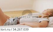 Woman relaxing on a bean bag indoors. Стоковое видео, агентство Wavebreak Media / Фотобанк Лори