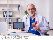 Old male doctor cardiologist in telehealth concept. Стоковое фото, фотограф Elnur / Фотобанк Лори